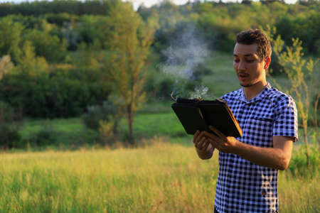White Caucasian young man or adult guy reading a burning book on blurred forest background. Foto de archivo - 153589503