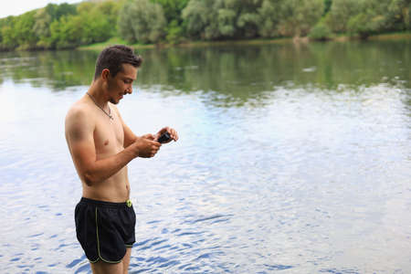A white Caucasian young man or adult guy with an action camera is filming on the river. Selective focus Foto de archivo
