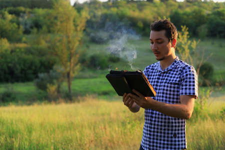 White Caucasian young man or adult guy reading a burning book on blurred forest background. Foto de archivo