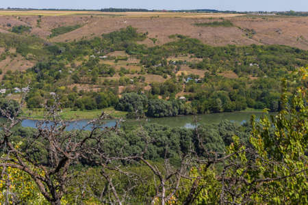View of the river from a huge hill or mountain through the eyes of a hiker on a hike. Green forest nature background. Selective focus. Foto de archivo - 153589697
