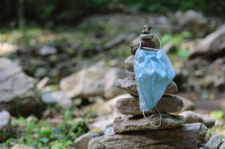 The medical surgical mask covers the pyramid of stones. Selective focus. The concept of travel and hiking during a pandemic. Standard-Bild
