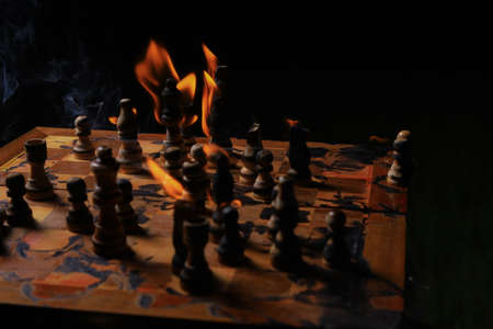 Burning chess pieces in the dark. Selective focus. Incorrect composition to create anxiety and tension in the artistic design.