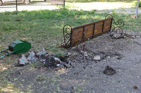Benches and trash cans broken by vandals in the park. The consequences of drunken fights