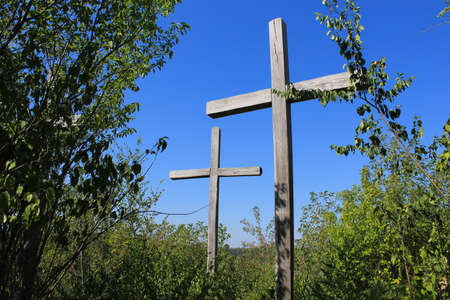 Silhouettes of old wooden crosses in contrasting sunlight. A pilgrimage site on a mountain in the forest. Religious travel to holy places, abstract background