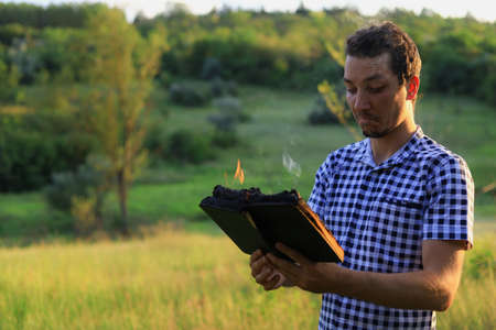 White Caucasian young man or adult guy reading a burning book on blurred forest background. Stock Photo