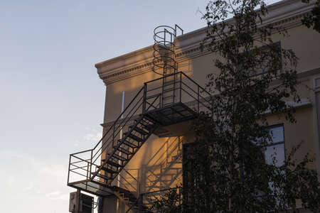 Fire escape with an emergency exit from the building in the rays of the evening sunset. Background