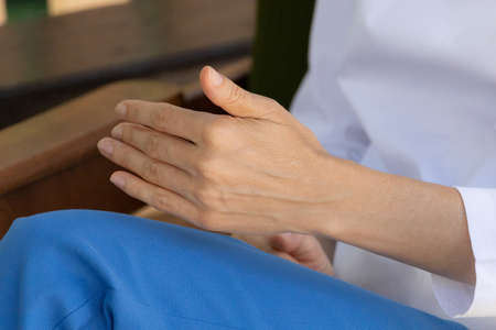 Consultation with a psychologist or psychotherapist. Close up of gesturing hands. Noise and grain as an artistic device imitating a freeze frame of a cinematic picture Stock Photo