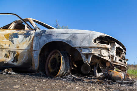 Burned down car, abstract background, selective focus. The situation of protests and pogroms in the world.