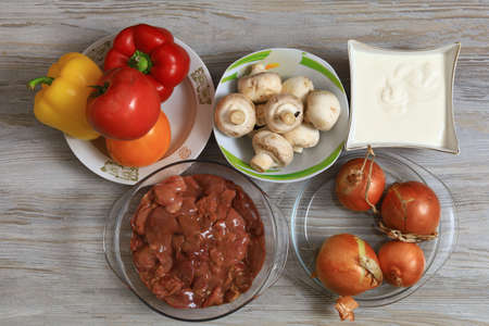 Vegetables with mushrooms and liver with sour cream. Ingredients for cooking. Culinary background with selective focus and blurred background.