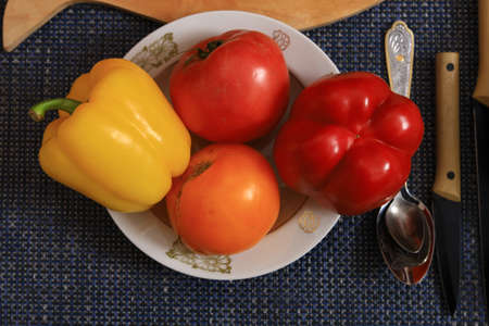 Sweet bell peppers and tomatoes. Culinary background with selective focus and blurred background.