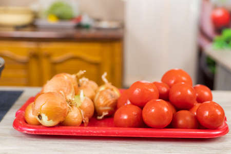 Onions and tomatoes. Culinary background with selective focus and blurred background.