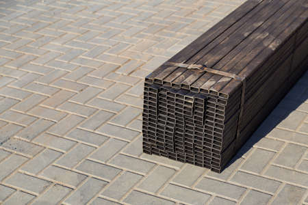 Rectangular metal pipes for building structures. Wholesale warehouse of a building base store. Background