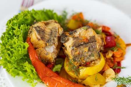Sea fish stewed with vegetables. Cooking healthy dietary meals at home during the lockdown.