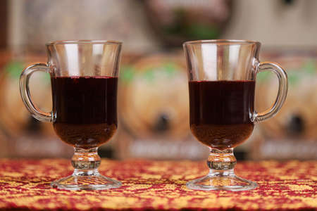 Two transparent mugs with mulled wine on a blurred background. Selective focus.