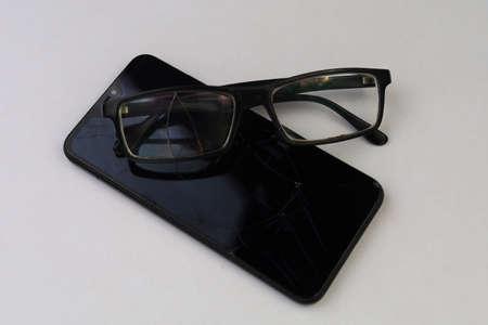 Broken glasses and smartphone. Selective focus. Background