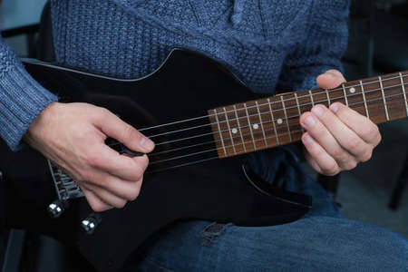 Hands of a guitarist with an electric guitar pick. Abstract music background