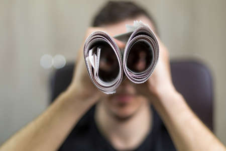 Man holding two twisted roll newspaper. Metaphor or allegory with binoculars. Selective focus on newspapers. Truth search concept