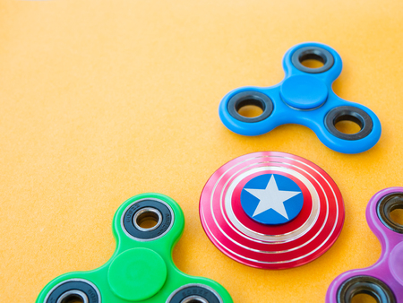 hyperactivity: Popular colourful fidget spinner toy on a colored background Stock Photo