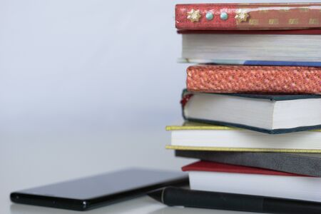 Stack of colorful books, open book and cup on wooden table. Back to school. Copy space Banco de Imagens