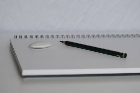 Pencil and notebook with space for text or image, selective focus. Blank notebook with pencil on white desk background. Banco de Imagens