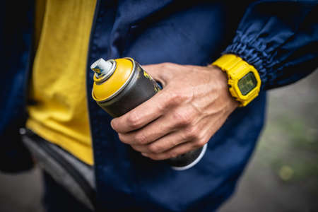 The artist in a blue jacket and a yellow watch holds a spray can of yellow paint in his hand 免版税图像