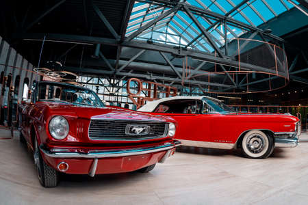 Cherry ford Mustang and red Codillac Eldorado in the building of the Museum of Retro Cars on Aprill 20, 2018 in Novokuznetsk, Kemerovo Region, Russian Federation.