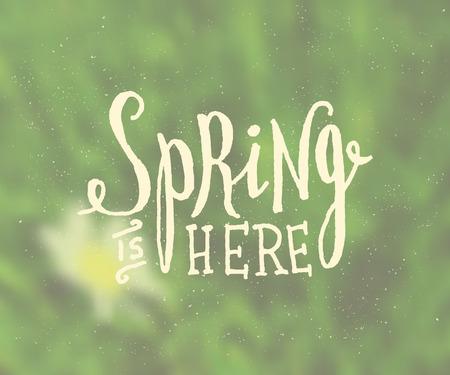 """� spring: Mano con letras del estilo del dise�o sobre un fondo borroso. """"La primavera est� aqu�"""" tarjeta de dise�o tipogr�fico."""