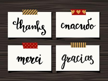 """te negro: Un conjunto de cuatro le agradece las notas en el fondo de madera. Letras de la mano """"Gracias"""" en diferentes idiomas - """"Spasibo"""" (en ruso), """"Merci"""" (franc�s), """"Gracias"""" (espa�ol)."""