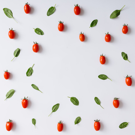 Tomates cerises et feuilles de basilic motif sur fond blanc. à plat.