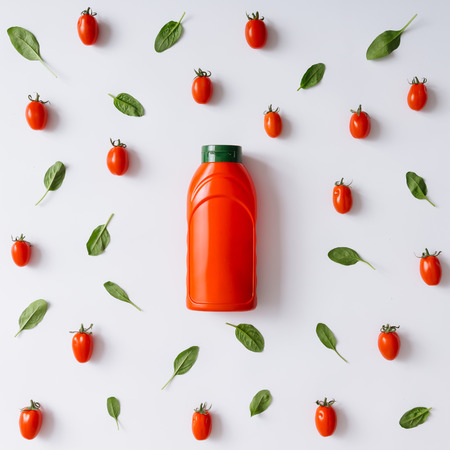 ketchup bottle: Ketchup bottle concept with cherry tomatoes and basil leaves pattern. Flat lay.