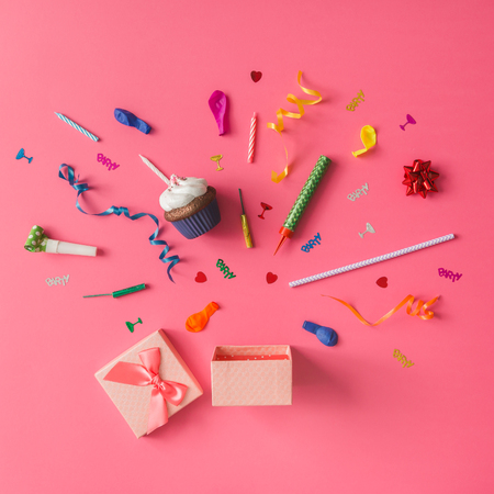 Gift box with colorful party items on pink background. Flat lay. Stock Photo