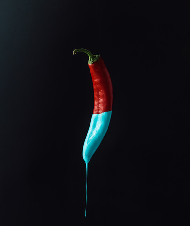 Red pepper with dripping blue paint on dark background. Minimal food concept.