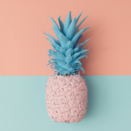 Pink pineapple on pink and blue pastel background. Minimal style. Food concept. Flat lay.