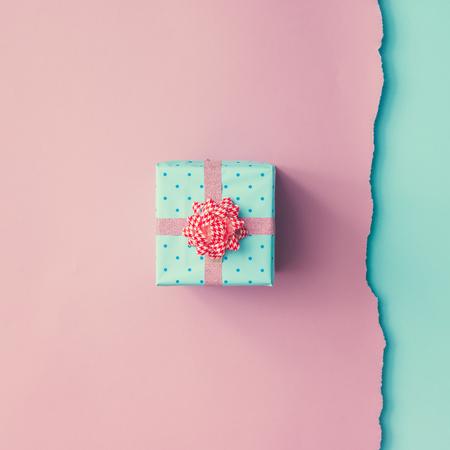 핑크, 블루 배경에 핑크 리본으로 포장 작은 선물의 총을 닫습니다. 크리스마스 배경입니다. 최소한의 개념. 플랫 누워. 평면도.