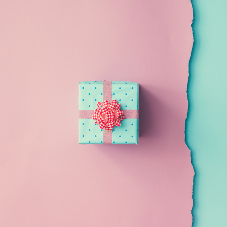 Close up shot of small gift wrapped with pink ribbon on pink blue background. Christmas background. Minimal concept. Flat lay. Top view. Фото со стока - 68075005