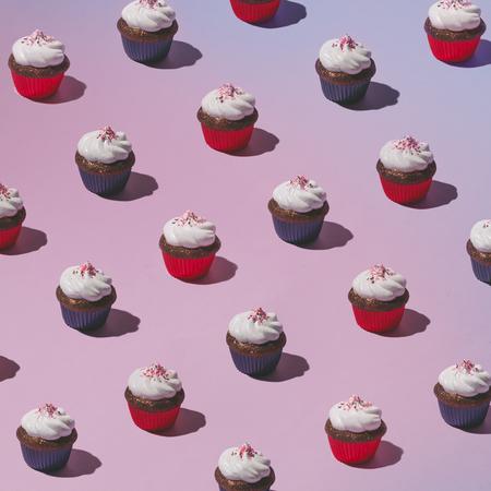 ピンクの背景にカップケーキのカラフルなパターン。最小限のコンセプトです。フラットが横たわっていた。 写真素材