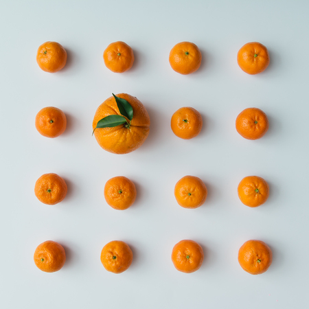 Creative pattern made of tangerines and orange on bright background. Flat lay minimal concept.