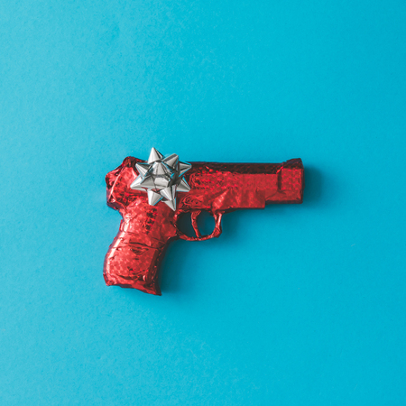 Gun wrapped in red paper with bow on blue background. Flat lay Christmas concept.