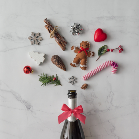 Champagne bottle with christmas decoration on marble background. Flat lay. Party concept.