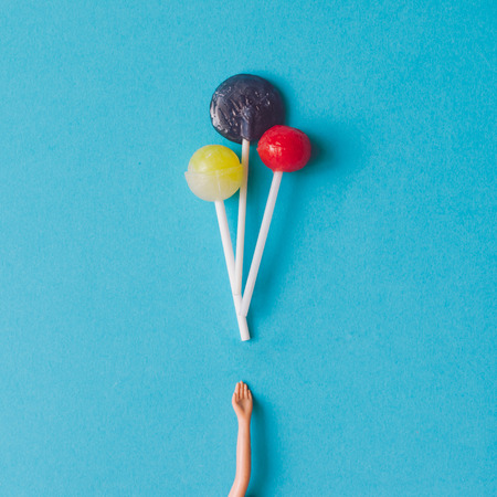 Doll hand with lollipops. Minimal concept. Flat lay. 版權商用圖片