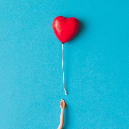 Doll hand met hart vormige ballon. Minimal concept. Plat.
