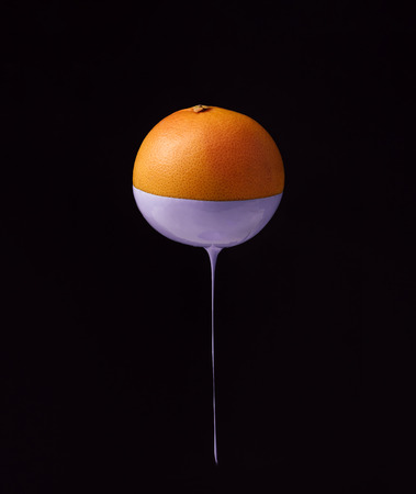 Grapefruit with dripping purple paint. Minimal food concept.