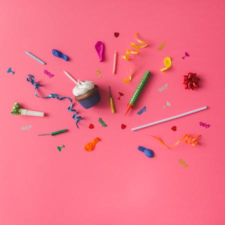 在粉色背景上的五顏六色的派對項目。平躺。