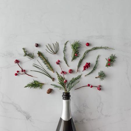 大理石の背景に冬の紅葉とシャンパンのボトル。フラットが横たわっていた。パーティーのコンセプトです。