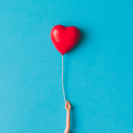 Doll hand with heart shaped baloon. Minimal concept. Flat lay. Stock Photo