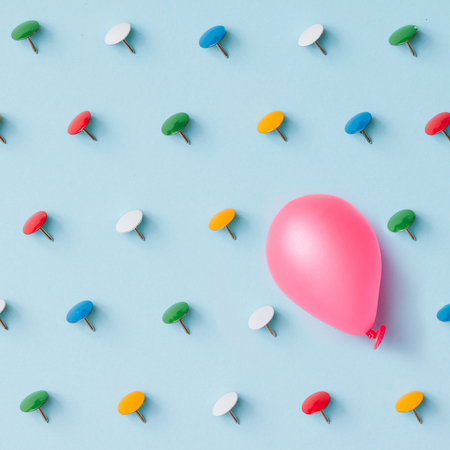 conquering adversity: Pink baloon with colorful pins on blue background. Adversity or unique concept. Flat lay. Top view.