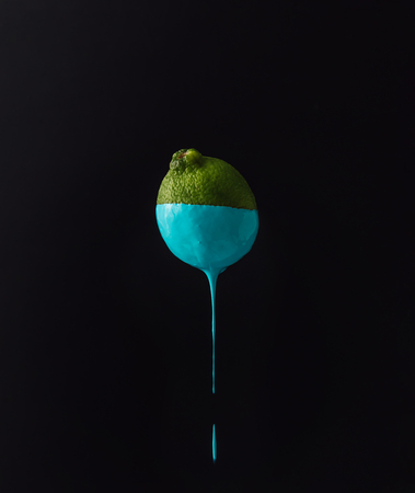 Lime with dripping blue paint on dark background. Minimal food concept.