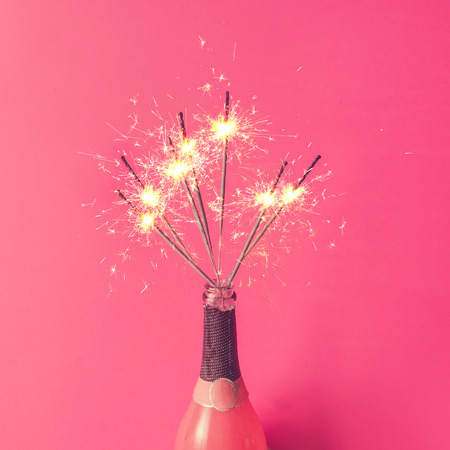 Бутылка шампанского с блестками на розовом фоне. Плоский лежал. Фото со стока