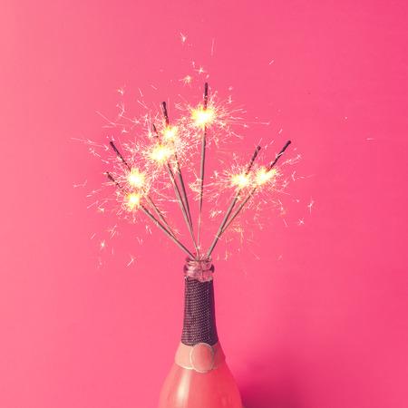 Champagne fles met sterretjes op roze achtergrond. Plat.