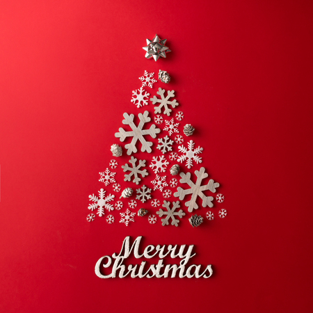 Christmas and New Years red background with Christmas Tree made of snowflakes. Holiday concept. Flat lay. Banque d'images
